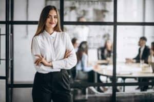 Eireli é uma empresa com único seocio representado no imagem por uma mulher empresária com sua equipe ao fundo.